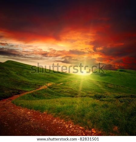 majestic sunset clouds and path through a mountain meadow to horizon