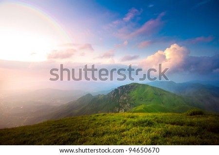 majestic sunset clouds and path through a mountain meadow to horizon - stock photo