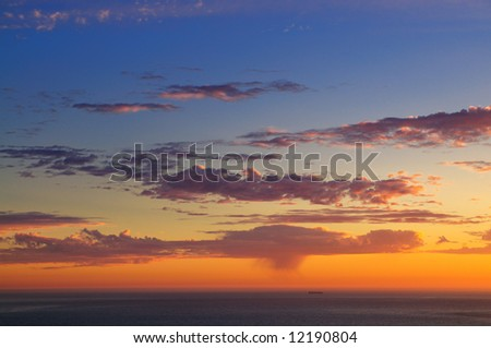 Majestic sunset over Pacific Ocean with a silhouette of a lonely ship far off and a rain squall visible in the distance.