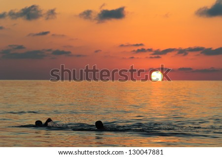 Majestic sunset over the Black Sea with swimmers on foreground