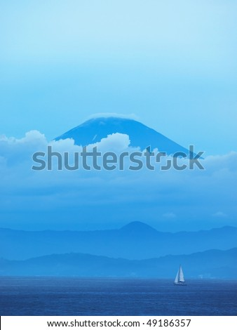 Majestic view of Mt.Fuji from other side of Sagami bay with hazy low clouds - stock photo