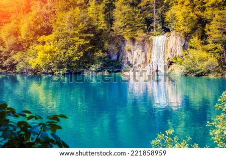 Majestic view on waterfall with turquoise water and sunny beams in Plitvice Lakes National Park. Forest glowing by sunlight. Croatia. Europe. Dramatic morning scene. Beauty world. Instagram effect. - stock photo