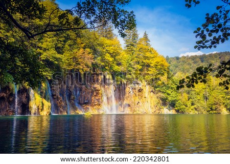 Majestic view on waterfall with turquoise water and sunny beams in the Plitvice Lakes National Park. Forest glowing by sunlight. Croatia. Europe. Dramatic morning scene. Beauty world.  - stock photo