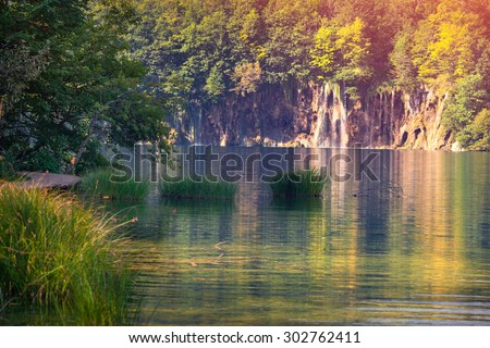 Majestic view on waterfall with turquoise water and sunny beams in the Plitvice Lakes National Park. Forest glowing by sunlight. Croatia. Europe. Retro style.
