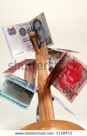 Major asian currencies arranged on a wooden pole. - stock photo