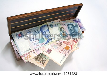 Major asian currencies filling up a wooden chest to the brim. - stock photo