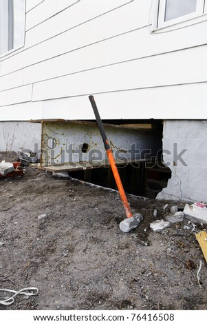 Major reno: sledgehammer against strong steel beam inserted for support to lift and old house with white siding to change the damaged concrete block foundation. - stock photo
