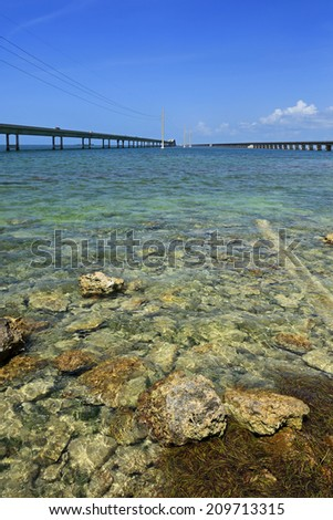 Major sections of the Florida Overseas Highway, and the Overseas Railroad it replaced, extend over shallow turquoise water. - stock photo