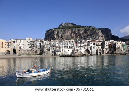 Major tourist attraction an old fishing village. The charm of an rowboat , old buildings, jetting rocks and mountain captured at Cefalu Beach. Located at the town of Cefalu, Sicily, Italy - stock photo