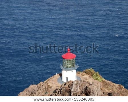 Makapu'u Lighthouse on cliffside mountain top with Blue pacific ocean below. - stock photo