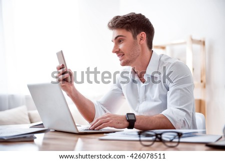 Make a call. Pleasant delighted handsome man sitting at the table anf using laptop while holding cell phone  - stock photo