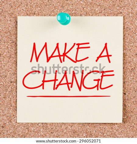 MAKE A CHANGE motivational quote written on a sticky note on corkboard.  - stock photo