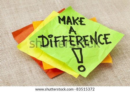 Make a difference -motivational reminder on green sticky note against canvas board