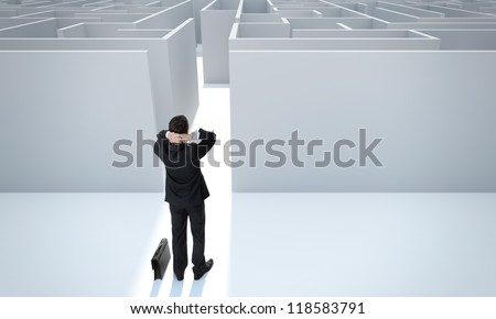 "Make a difficult decision. Achieving the goal. Without the sign ""Welcome"" on the wall. Encounter difficulties. Businessman standing in front of the entrance to the maze. - stock photo"