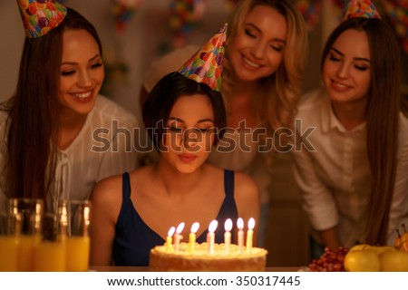 Make a wish. Young attractive girl is about to make a wish and blow all candles.