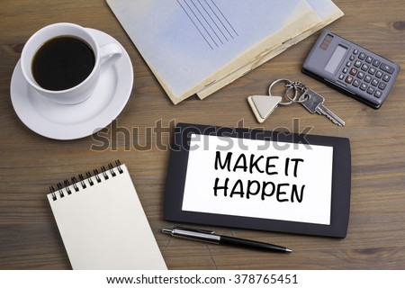 Make It Happen. Text on tablet device on a wooden table - stock photo