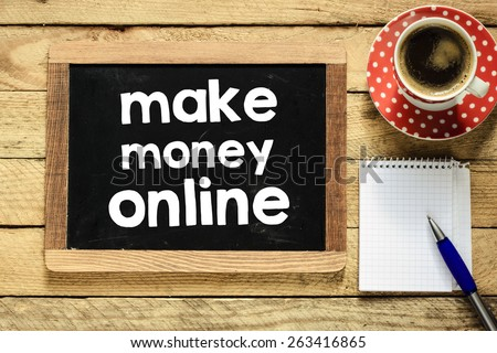 Make money online on blackboard. Make money online On blackboard with cup of coffee, notebook and pen on wooden background - stock photo