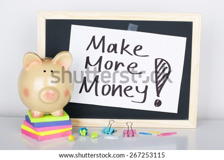 Make More Money / Motivational phrase about financial growth on chalkboard with piggy bank - stock photo