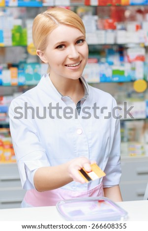 Make purchase with the credit card. Young smiling blond pharmacist stretching out a credit card looking at the camera - stock photo