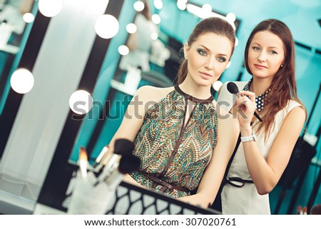 Make-up artist and model at work in front of mirror, reflection
