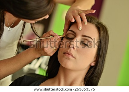 Make-up artist applying bright base color eyeshadow on model's eye - stock photo