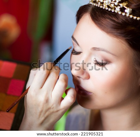 Make-up artist applying bright base color eyeshadow on model's eye and holding a shell with eyeshadow on background, close up - stock photo