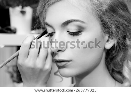 Make-up artist applying color eyeshadows on model's eye, close up. Black and white - stock photo