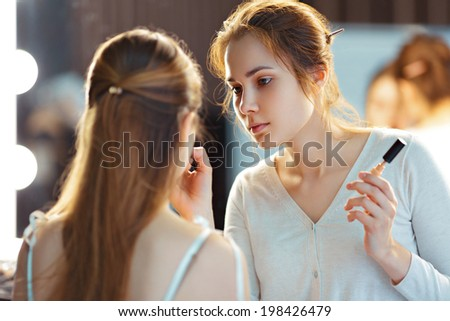 Make-up artist applying consealer, selective focus on MUA - stock photo