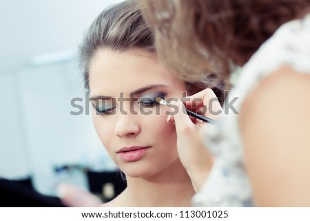 Make-up artist applying  dark eyeshadow on model's outer corner of the eye, selective focus, close up - stock photo