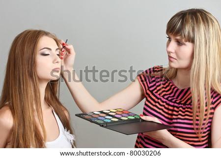 Make-up artist applying eye shadows on beautiful model - stock photo