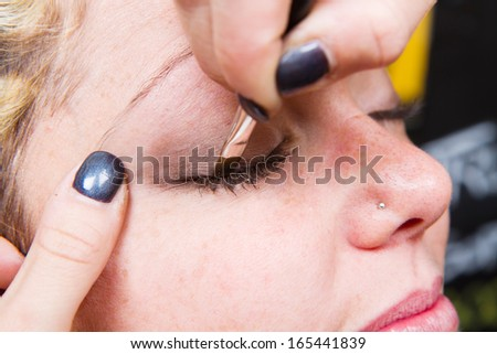 Make-up artist  applying eyebrow make-up - stock photo