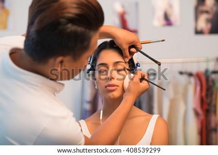 Make-up artist applying eyeshadows on the outer corner of the eye - stock photo