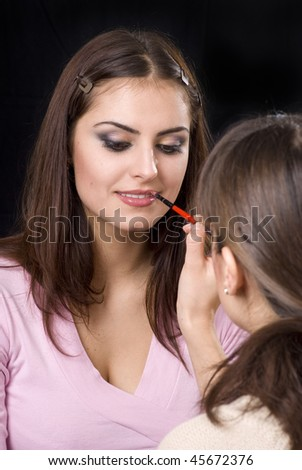 Make-up artist applying lipstick to a young woman - stock photo