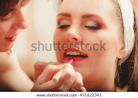 Make up artist applying lipstick with brush on pretty gorgeous woman lips. Closeup of visagiste and young girl. Beauty and makeup concept. - stock photo