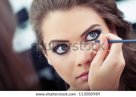 Make-up artist applying liquid eyeliner with brush, close up - stock photo