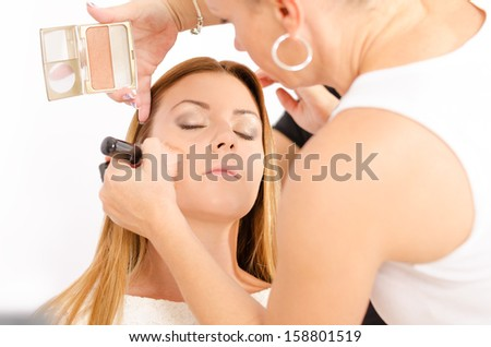 Make up artist applying make up and a hairdresser preparing the hair on a young and beautiful female model  - stock photo