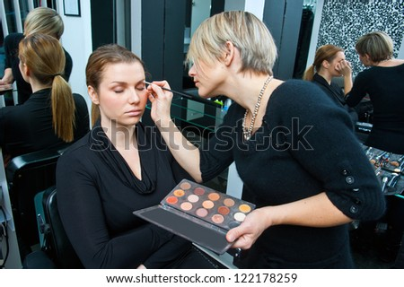 make up artist applying make up on model - stock photo