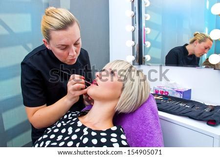 make up artist applying make up on model lips - stock photo