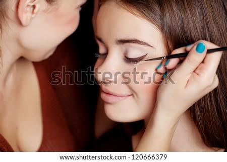 Make up artist applying make up to a fashion model - stock photo