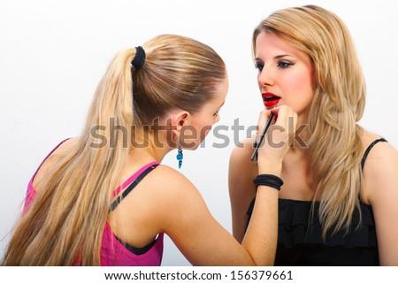 Make-up artist applying mascara on model's lips - stock photo