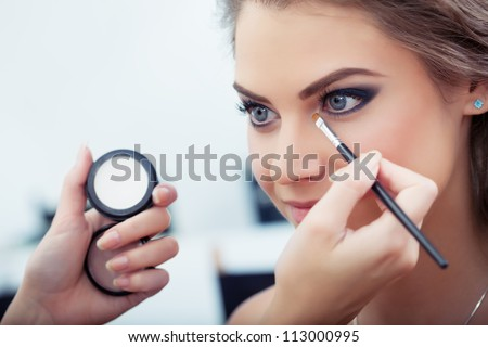 Make-up artist applying white eyeshadow in the corner of model's eye and holding a shell with eyeshadow on background, close up - stock photo