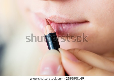 make up artist colors lip contour using a stick - stock photo