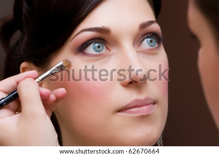 make up artist makeing a colour correction with an brush to the beautiful young lady bride - stock photo