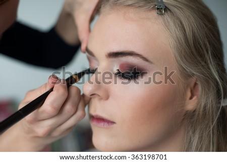 Make-up artist preparing model for the fashion photoshot - stock photo