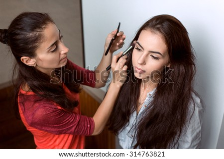 Make-up artist work in her studio, paints a model - stock photo