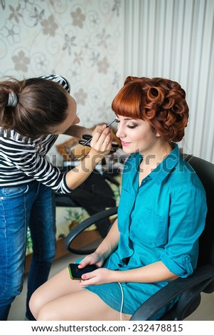 Make up artist working on her model - stock photo