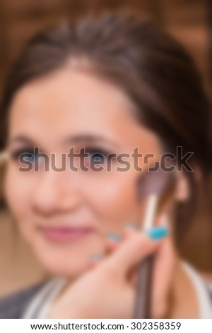 Make-up artist working with the model. Blurring background. - stock photo