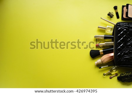 make up bag with cosmetics and brushes on green background. top  - stock photo
