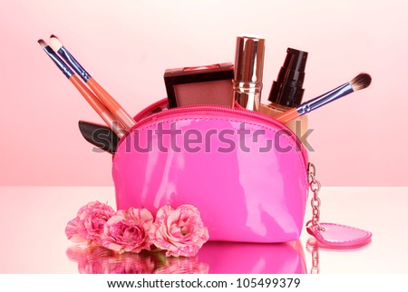 Make up bag with cosmetics and brushes on pink background - stock photo