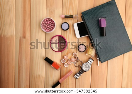 Make up bag with cosmetics on wooden background - stock photo